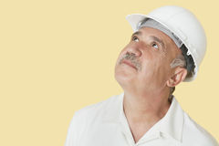 Senior construction worker with hardhat looking up over yellow background Stock Photos
