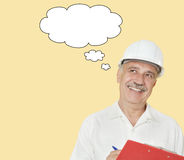 Senior constructor with clipboard looking away over yellow background Stock Photo