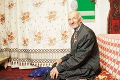 Senior contented man on sofa Stock Photos