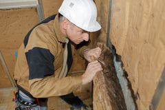 Senior contractor fitting wall insulation. Man stock photo