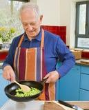Senior cooking. Senior man cooking in his kitchen Stock Image