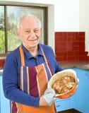 Senior cooking. Senior man cooking in his kitchen Royalty Free Stock Photos