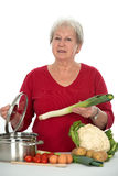 Senior is cooking Stock Images
