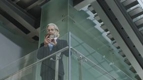 Caucasian businessman using mobile phone. Senior corporate executive standing on second floor in modern office building dialing numbers using cellphone Royalty Free Stock Photos