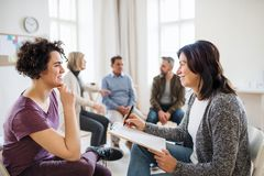 Senior counsellor with clipboard talking to a woman during group therapy. A senior counsellor with clipboard talking to a young women during group therapy royalty free stock photography