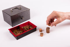 Senior counts money of an old cashbox. Senior counts the coins of an old cashbox. It seems to be a bad time for seniors with little money. Little pension for a Royalty Free Stock Image