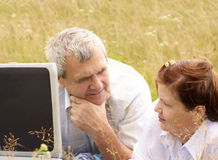 Senior couple. With laptop on the meadow Stock Photography