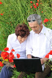 Senior couple. Happy senior couple spending time on laptop outdoors Royalty Free Stock Images