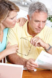 Senior couple. Working with laptop at home Stock Photos