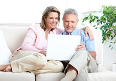 Senior couple. Working with laptop at home stock photo