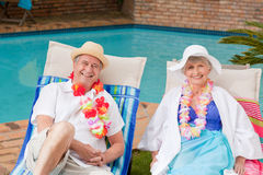 Senior couple. Lying down beside the swimming pool royalty free stock photos