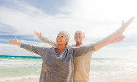 Senior couple. Happy senior couple with outstretched arms enjoying retirement