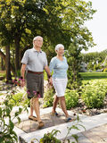Senior couple. Senior Caucasian couple holding hands and walking outdoors in park Stock Photography