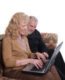 Senior couple. Enjoying looking at images of their family on a laptop computer Royalty Free Stock Photo