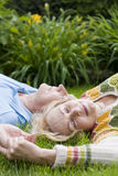 Senior couple - 42 years in love. Senior couple laying on the grass stock photos