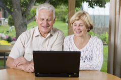 Senior couple - 42 years in love. Smiling senior couple using laptop at home royalty free stock photography