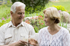 Senior couple - 42 years in love. Senior couple drinking champagne in a blossoming garden royalty free stock image