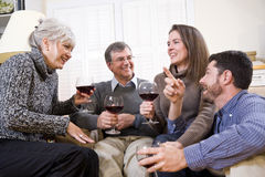 Senior couple, adult children talking and drinking royalty free stock image