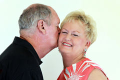 Senior couple affection. A senior man kissing a senior woman on the cheek on a white background royalty free stock photography