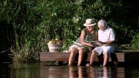 Senior couple with album outdoors. stock video