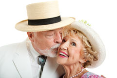 Southern Senior Couple Kissing. Senior couple from the American South.  He's kissing her on the cheek.  White background Royalty Free Stock Image