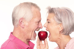 Senior couple with apple Stock Photos