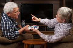 Senior couple arguing over TV remote control. Senior married couple sits in front of television in arguing over who gets to have the remote control. Horizontal Royalty Free Stock Images