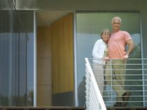 Senior couple arm in arm on balcony, smiling, portrait, low angle view Stock Image