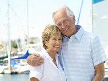 Senior couple arm in arm by boats, smiling, portrait Royalty Free Stock Images