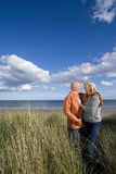 Senior couple arm in arm on sand dune, smiling at each other, side view Stock Images