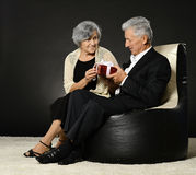 Senior couple  in armchair  with gift Stock Photo