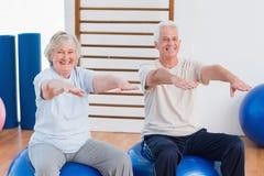 Senior couple with arms raised sitting on exercise ball. Portrait of senior couple with arms raised sitting on exercise ball at gym Royalty Free Stock Photo