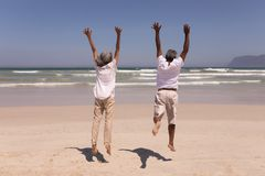 Senior couple with arms up jumping on beach royalty free stock photos
