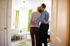 Senior couple arrive embracing in a hotel room, back view Royalty Free Stock Photo