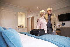 Senior Couple Arriving In Hotel Room On Vacation Stock Photo