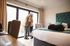 Senior Couple Arriving In Hotel Room On Vacation Stock Image