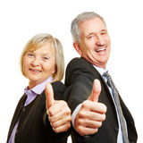 Senior couple as businesspeople holding thumbs up Stock Image