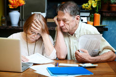 Senior Couple At Home With Many Bills Royalty Free Stock Photos
