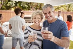 Senior couple at a backyard party raising glasses to camera royalty free stock photos