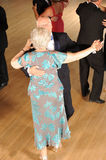 Senior couple ballroom dancing. With other couples in background on dance floor Stock Image