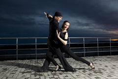 Senior couple ballroom dancing on dark sunset. Background Stock Image