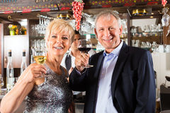 Senior couple at bar with glass of wine in hand. Senior couple in restaurant standing at bar with glass of wine in hand and having fun Royalty Free Stock Image