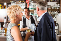 Senior couple at bar with glass of wine in hand. Senior couple in restaurant standing at bar with glass of wine in hand and having fun Royalty Free Stock Photography