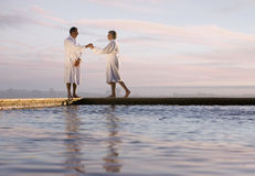 Senior couple in bathrobes on edge of swimming pool at dawn, low angle view Royalty Free Stock Photography