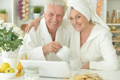 Senior couple in a bathrobes with laptop Stock Images