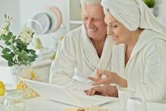 Senior couple in a bathrobes with laptop Royalty Free Stock Photos