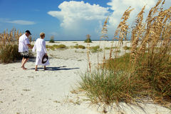 Senior couple on beach. Senior couple walking on the sandy beach royalty free stock photo