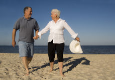 Senior couple on beach. Smiling senior citizen couple looking at one another and holding hands as they walk on a sandy beach toward the viewer