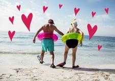 Senior couple on beach with digitally generated pink hearts. Rear view of senior couple on beach with digitally generated pink hearts Royalty Free Stock Photography