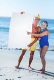 Senior couple with beach equipment holding a white poster Stock Photos